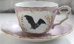 GORGEOUS BAT TEACUP AND SAUCER SET This teacup and saucer set will be infused with the image of a lovely bat. Fully food- and dishwasher-safe, wear-resistant. The border is a scrolled gold with pink (or green) accents. Pink Und Gold, Green And Gold, Outside Tiles, Style Deco, Tile Murals, Vintage Plates, Vintage Teacups, Green Accents, Teller