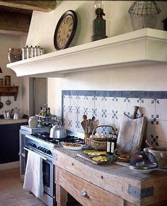 Large stove prep area with butcher block table and range hood with shelf