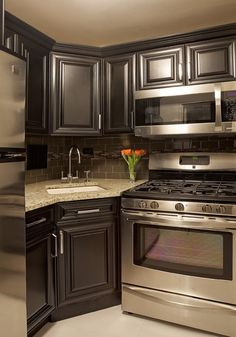 My next kitchen. Dark grey cabinets with dark backsplash, stainless appliances and granite countertop