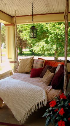 Should have built this years ago.....an old futon mattress, old curtains sewn together to make a cover, old tablecloth cut up to cover chains, several old throw pillows.....& WahLah!!!  Heaven on my front porch.....