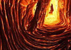 """Lava Cave • Hawaii  Lava caves are formed when lava runs down the side of a volcano. The upper part cools and the lower part continues to flow below the surface in a tube-like form, creating a """"cave"""". This image of a newly forming lava cave was quite difficult for the photographer to take, the yellow center being around 2000°F, the darker parts being close to 800°F. (by: Leigh Hilbert)"""
