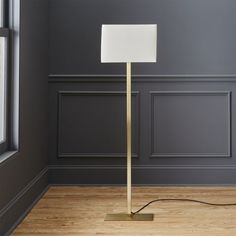 Shop john metallic bronze floor lamp.   Sleek proportions square up in a contrasting mix of industrial and ethereal.  Rectangular steel base ascends a bronze metallic finish haloed by crisp white cotton box shade.