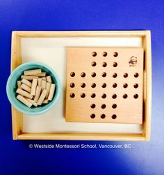 Montessori Practical Life activity - placing wooden pegs onto a board. The shape of the pegs are perfect for developing the muscles in the pincer grip, in preparation for holding a pencil.