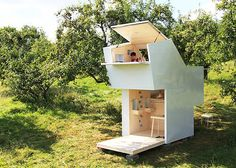 This adorable tiny home has a glossy white exterior, plywood interior, built in storage, and walls that fold up to fully enclose the space.