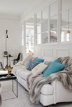 bright-blue-and-yellow-patterned-scatter-cushions-with-faux-fur-throw-on-cosy-sofa