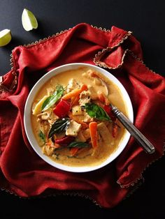 Instant Pot Thai Red Curry with Chicken with spoon on a black background with lime, placed on a red and gold napkin- Paint the Kitchen Red
