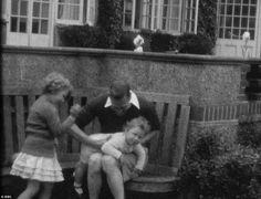 H.M. King George VI plays with his daughters H.R.H. Princess Elizabeth (later H.M. Queen Elizabeth II and H.R.H. Princess Margaret (later H.R.H. Princess Margaret, Countess of Snowdon.)