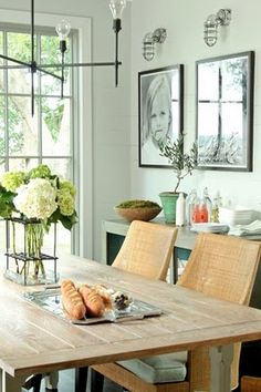 Gorgeous coastal dining room. Love the woven chairs, pale seafoam green wall colour and industrial style lighting.