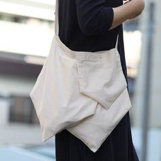We'll bring you our products only made by hand work from a small room. 私たちは小さな部屋から手作りだけをお届けします。.大きバッグが2つと小さいバッグが1つ 3つのバッグがくっついているデザインです 上部のみ縫いとめているのでゆるっとした感じです ズラしてくっつけているので肩にかけると面白い形になります.小さいバッグはスナップボタンが付いてます 薄手の素材なのでとても軽いです 小さく畳んで携帯するにも便利です ストラップは好きな長さに結んで色んな持ち方が出来ます.▽サイズ 大きいバッグ → 横:約330mm × 縦:約400mm(最長) 約250mm(最短)      小さいバッグ → 横:約200mm × 縦:約230mm(最長) 約150mm(最短)      ストラップ:約900mm▽素材  綿100%▽色   生成り