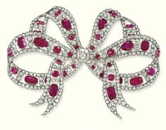AN ELEGANT EDWARDIAN RUBY AND DIAMOND BOW BROOCH   The openwork ribbon with vari-shaped ruby and old-cut diamond collets to the scalloped sides and cushion-shaped diamond centre weighing 2.17 carats, mounted in silver and gold, brooch fitting detachable, circa 1905, 8.5 cm wide