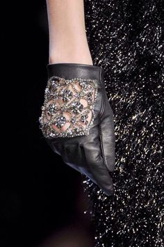 Black leather wristlet gloves. The back of the glove has intricate cutwork designs and is studded with rhinestones