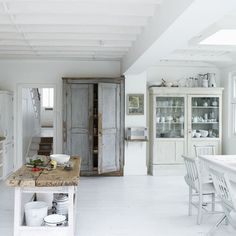 Really nice white, fresh, clean kitchen. The rough/rustic cabinet and table are amazing.