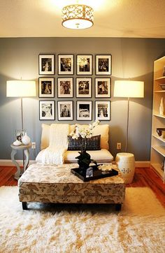 Black and White photos on white matte board with black frames perfectly arranged on a wall.  Love that ceiling light too.  Cute seating space for a small area.  Paint color is Santorini blue by Benjamin Moore.