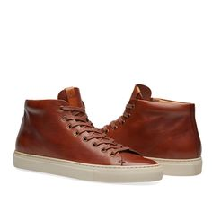 Buttero deliver the best traditions of Italian shoemaking by refining footwear with superior and locally sourced leathers. Handmade by craftsman in Tuscany, the calf leather uppers of these mid top sneakers will age beautifully over time – just like the region's fine wine. Marking the quality, the branded leather patch on the tongue and padded leather insole round off the quality, perfectly fusing rawness with pure elegance.  Leather Uppers Cotton Laces Padded Leather Insoles Embossed Tongue…