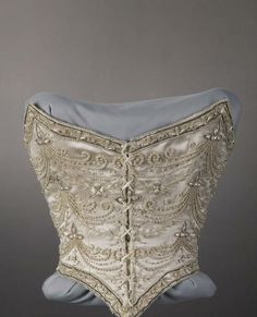 Date 1896 Description Bodice, wedding-style, of white silk satin embroidered with white silk floss, silver-colored mesh, rhinestones, pearl beads, and silver-colored cording. Pointed waist at front.