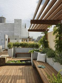 | Zen rooftop terrace designed with wood planks, natural shrubs, water fountain, and bench, surrounded by sand and stone. |