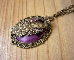 Adorable Steampunk necklace featuring a polymer clay cabochon and an antique brass peacock in a beatiful ornate setting.    The charm measures 3x4c...