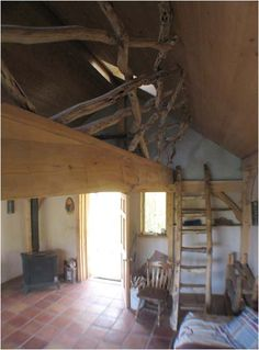 Love the wood railing for the loft in this cob house.