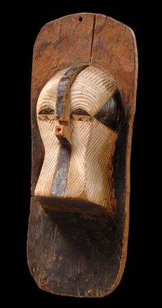 """D. R. Kongo, Songe  Holz, matte Patina, schwarze und weiße Farbe, abgerundete Rechtecksform, mittig vorgeblendete Maske """"kifwebe"""" mit niedrigem Stirnkamm und vorspringendem Mund, komplette Maske mit parallelen Ritzverzierungen überzogen, min. besch., Riss, Abriebspuren, auf Sockel montiert; sie erfüllen eine zweifache Funktion: zum einen als Tanzmaske und zweitens als Emblem der """"bifwebe""""-Gesellschaft, um an der Wand oder an einem Zaun aufgehangen zu werden. H: 38 cm"""