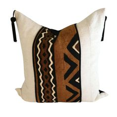 The rust color in the pillow is reminiscent of the hearty red clay of the African continent which symbolizes Mother Nature.   The bold anchor color is then combined with solid white mud cloth for balance.   Black tassels have been added for a posh contemporary look.   The back of the pillow is made of black Irish linen and it is closed with an invisible zipper.