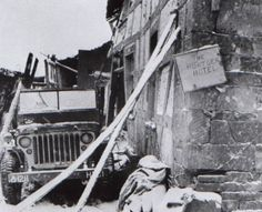 """A farmhouse on the main route through Hürtgen served as shelter for HQ Company, 121st Infantry Regiment, 8th Infantry Division, XIX Corps, 9th US Army, as indicated on the bumper of the jeep. They nicknamed it the """"Hürtgen Hotel"""""""