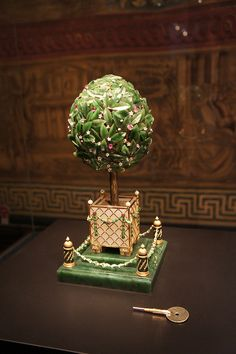1911 / The Bay Tree Egg is made of gold, green & white enamel, nephrite, diamonds, rubies, amethysts, citrines, pearls & white onyx.  The topiary tree is carved nephrite, finely veined leaves & jeweled fruit & flowers on an intricate framework of branches, the fruits are champagne diamonds, amethysts, pale rubies & citrines; the flowers white enamel & set with diamonds.  A keyhole & tiny lever, hidden among the leaves, open the hinged circular top of the tree - a bird rises up, flaps its…