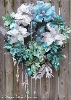 "Blue, light turquoise and large silver poinsettia make our ""Winter Wonderland"" an elegant wreath for your front door or indoor wall decor. Blue and silver ornaments add a reflective quality. Iridescent icicles hang suspended on shimmering narrow ribbon. A lush white tipped evergreen base, silver accents and snow touched pine cones and long needled pine boughs plus a large sheer blue bow with just the right amount of glitter and shine complete the arctic winter look."