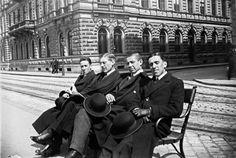 V., padon ücsörgők a Rudolf (ma Széchenyi) rakparton a Széchenyi utca torkolatánál; 1913. április, André Kertész felvétele (culture.gouv.fr).  1913.  Széchenyi (Rudolf) rakpart a Széchenyi utcánál. Kertész André képe. A padon a fénykép készítőjének kollégái ülnek.
