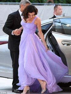 Careful: Amal ensured her luxurious gown wasn't caught on the car door
