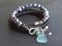 Multi-wrap pearl and Leather bracelet with bright peacock pearls and silver charms.  A circle of 6-8mm Baroque pearls adorn this multi wrap bracelet. Finished with aqua sea glass, blue opal bead and recycled silver charms. 4mm natural leather cord sterling end caps, and a oversized hook clasp make it easy to open and close with one hand. One of a kind style that circles the wrist 4 times at 28 inches. Ask for custom sizing.