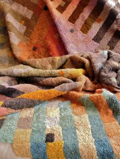"""Knitted Blanket by Mona Abdel-Rahman: """"Raw fleece: 3 days to wash and dry; about 2-3 years to hand-card the wool and spin on a Turkish drop-spindle; at least two 5-10 day sessions of natural dyeing; another 2 weeks skeining the wool; 7 months to knit the blanket; one afternoon to machine wash and """"full"""" (shrinking process to make it more durable); 5 minute photo shoot; priceless."""""""
