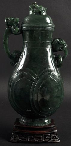 A GOOD EARLY 20TH CENTURY CHINESE GREEN SPINACH JADE VASE AND COVER  -- carved with a recumbent bird finial, the handle with kylin mounts. Natural fissures. Jade 9.75ins high.