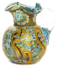 A Moser water pitcher having a prussian blue body decorated with gold scrolling and polychrome flowers, applied crystal handle. Czechoslovakia, circa 1893-2005
