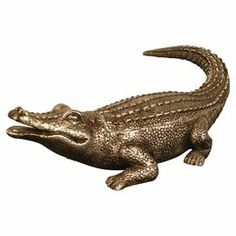"Bronze-finished trinket box with an alligator shape.   Product: Trinket box   Construction Material: Composite wood   Color: Bronze  Dimensions:  4"" H x 3.75"" W x 11"" D"