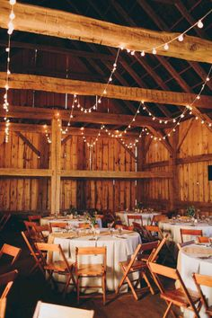 Barcelona lights strung from the barn rafters create a warm ambiance at a Historic Barns of Nipmoose wedding reception. Photography by Lisa Woods