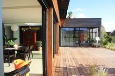 La grande pièce à vivre à la façade complètement vitrée donne directement sur la large terrasse pour vivre dedans-dehors toute l'année.