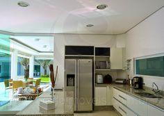 Equipada com refrigerador duplex, eletrodomésticos em aço inox, armários planejados e bancada em granito, a cozinha é enorme e muito bem arejada.
