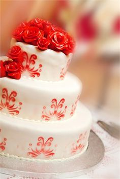 A three tier wedding cake that has been decorated with iced orange flowers and elegant orange detail on each tier.