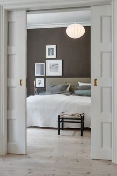 Grey, beige & tobacco brown is not a common colour combination.  Light-grey sliding doors, tobacco brown wallpaper & what i find most inspiring, frames that follows the shape of the headboa...