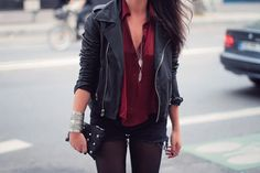 Leather jacket, silk blouse, denim shorts and tights with silver jewelry.