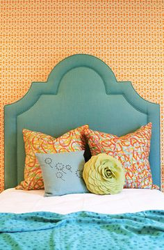 girl's bedroom with orange wallpaper + blue upholstered headboard // design by Lucy and Company #bedroom #wallpaper #orange