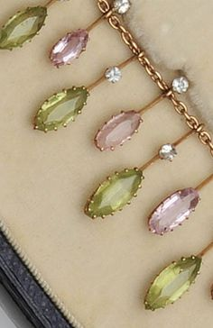 A late Victorian fringe necklace The belcher-link chain suspending a fringe of alternate oval-cut pink topaz and marquise-cut peridot drops, claw set, with round-cut aquamarine highlights, in fitted case, length 36.5cm.