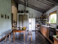 Globally-Inspired Kitchen Design | Patterned blue-and-white floor tiles, colorful Indonesian painted doors, and brass-accented hanging lanterns give it a subtle ethnic flavor without resorting to pastiche.