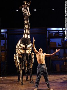 """Actor Sandile Matsheni performs with a giraffe puppet in """"Tall Horse,"""" a Handspring Puppets Company production at The Baxter Theatre, Cape Town, in 2004."""