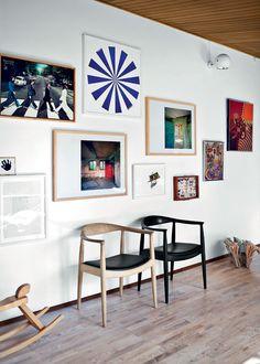 Grafik og fotokunst, et aftryk af en barnehånd og en sommerfuglesamling. En uhøjtidelig blanding, der klæder de to The Chair stole af Wegner. Her hænger grafik og fotokunst af bl.a. Henrik Plenge Jakobsen og Søren Lose.