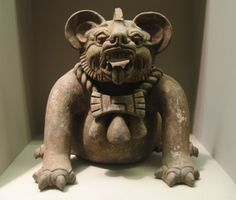 """""""A funerary urn in the shape of a """"bat god"""" or a jaguar, from Oaxaca, dated to AD 300–650. Height: 9.5 in (23 cm."""" The bat part refers only to the face, while the body is that of a jaguar, and it wears a decorative necklace. Zapotec."""
