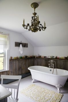 Home Tour: Tata Harper in Vermont. A chandelier hangs above a classic clawfoot bathtub.