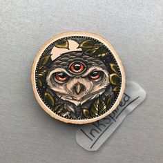Wood slice with an original drawing of an owl with third eye