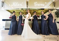 Bride's model-style pose with her wedding party at the bar