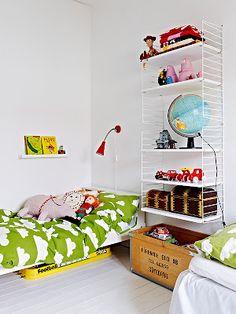Att köpa. Hyllor på väggen på båda barnens sidor som sen kan utökas med skrivbordsskivor, under hyllorna två trälådor med hjul och tryck med barnens namn och födelseår.